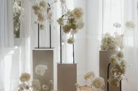 a refined minimalist wedding altar of tall white stands with tall white floral arrangements is a gorgeous idea for a delicate minimal wedding