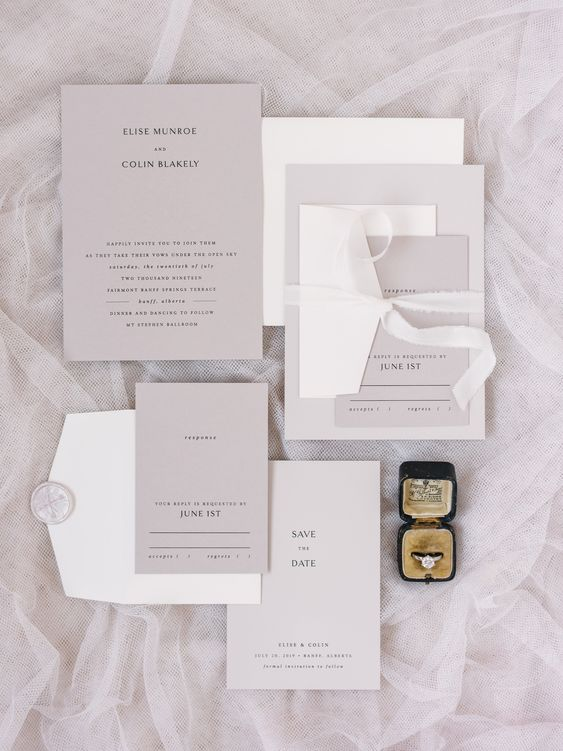 a refined minimalist wedding invitation suite in grey and white, with black lettering and white ribbons and stamps is cool