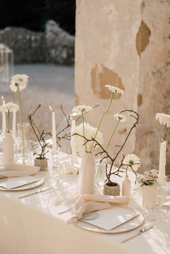 a refined minimalist wedding table setting done in warm neutrals, with blooms, willow, elegant linens and chargers is cool