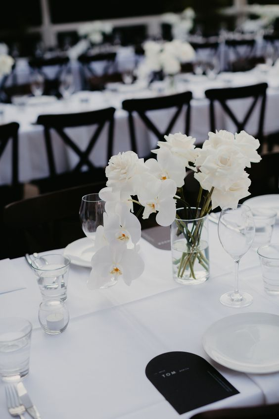 a refined minimalist wedding tablescape with crispy white linens, white roses and rochids, white plates and black menus