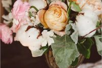 a refined wedding centerpiece of a gilded vase with pink, yellow and orange blooms, foliage and cotton is a beautiful solution