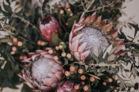 a relaxed and pretty wedding bouquet of king proteas, lots of greenery branches and berries is great for a summer wedding