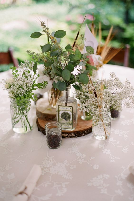 a relaxed cluster wedding centerpiece of vases and bottles with greenery, baby's breath, cotton and some candles around is chic