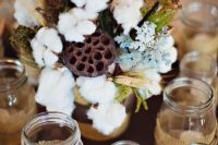 a rustic centerpiece with pale miller, wheat, cotton and greenery plus lots of candles in jars around for a fall or winter wedding