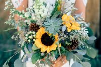a rustic wedding bouquet of sunflowers, white blooms, berries, billy balls, pinecones, a succulent and lots of greenery is great for both fall and summer