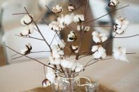 a rustic wedding centerpiece of a jar with cotton branches and candles around is a simpel and very cute solution for a rustic wedding
