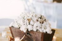 a rustic wedding centerpiece of a rich-stained wooden box filled with cotton, candles and antlers is a gorgeous idea to go for