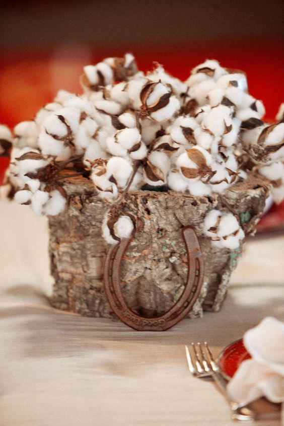 a rustic wedding centerpiece of a tree stump filled with cotton and a horseshoe is a lovely and cozy idea that you can DIY