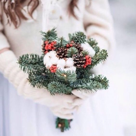 a simple rustic wedding bouquet with evergreens, cotton, pinecones and holly berries can be easily DIYed by you