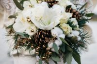 a small and elegant ball-shaped winter wedding bouquet of white blooms, greenery, cotton, gilded pinecones, berries and grasses is wow