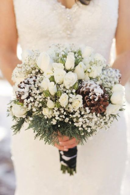 a snowy winter wedding bouquet of white baby's breath, white roses, evergreens and pinecones is a cool solution for winter