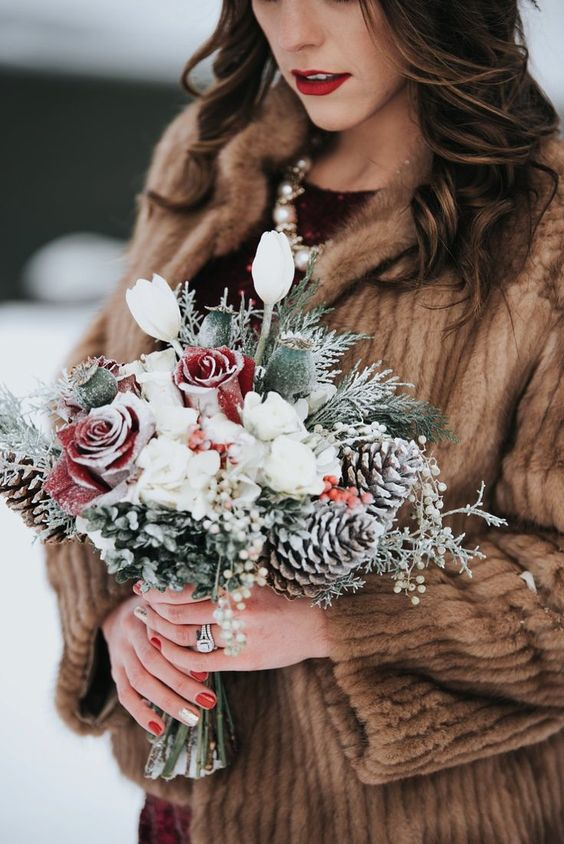 a snowy winter wedding bouquet of white blooms and snowy red roses, greenery, pinecones and seed pods is a gorgeous idea for winter