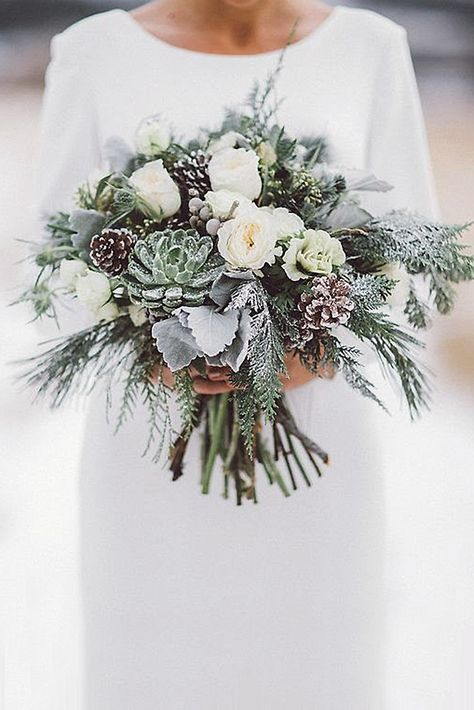 a snowy winter wedding bouquet of white blooms, succulents, pale leaves, evergreens, berries and pinecones is a gorgeous idea