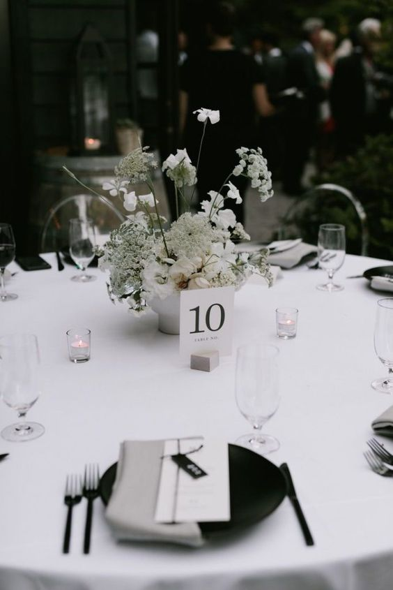 a sophisticated minimalist wedding tablescape with a crispy white tablecloth, blakc plates and grey napkins, neutral blooms and candles