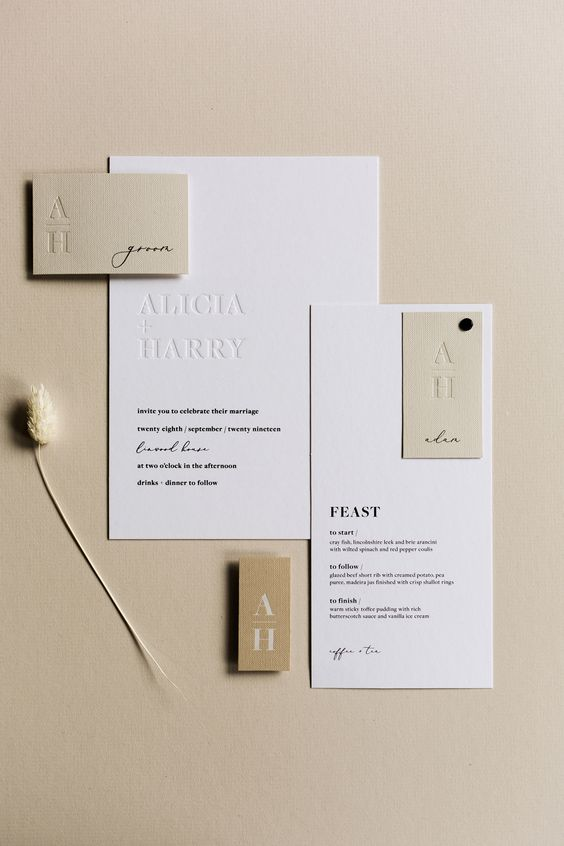a stylish contemporary to minimalist wedding invitation suite in white and tan, with stylish black letters and letter pressing is chic
