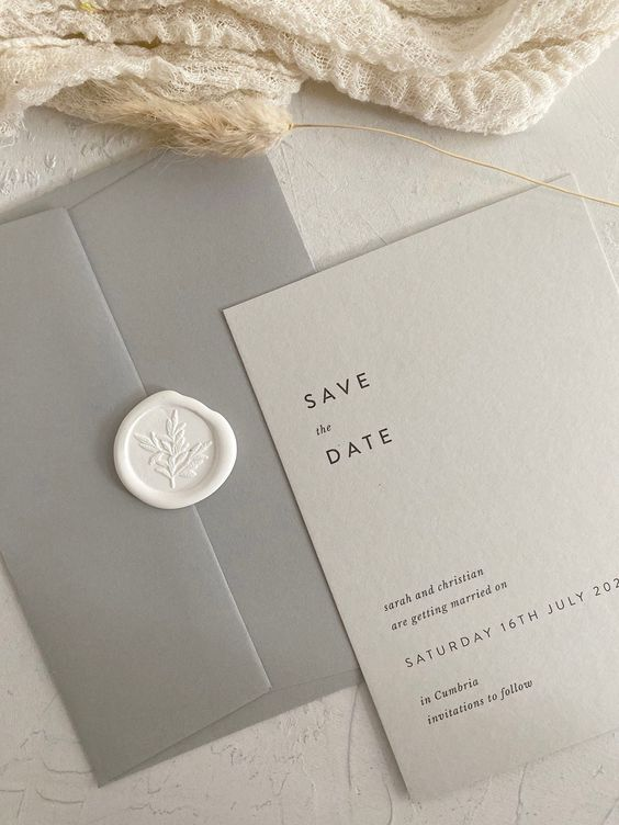 a stylish light grey and grey save the date suite with simple black lettering and a white stamp is a cool and chic minimalist idea