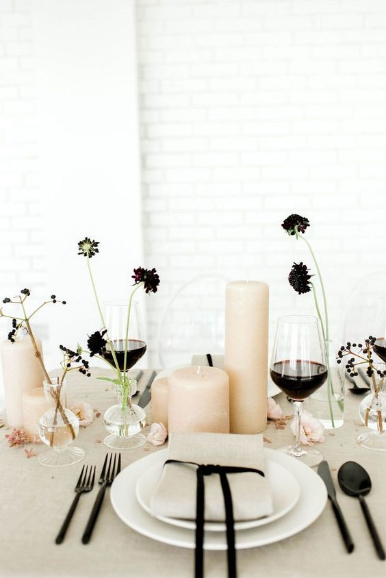 a stylish minimalist wedding table setting with grey linens, white plates, blush pillar candles, black blooms and berries and black cutlery