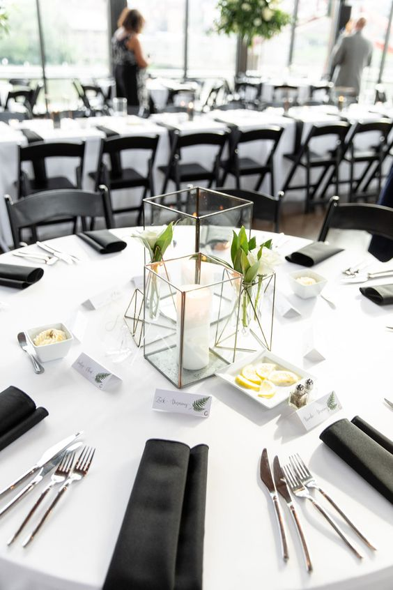 a stylish minimalist wedding tablescape with candle lanterns with blooms and a candle, with black napkins and a white tablecloth