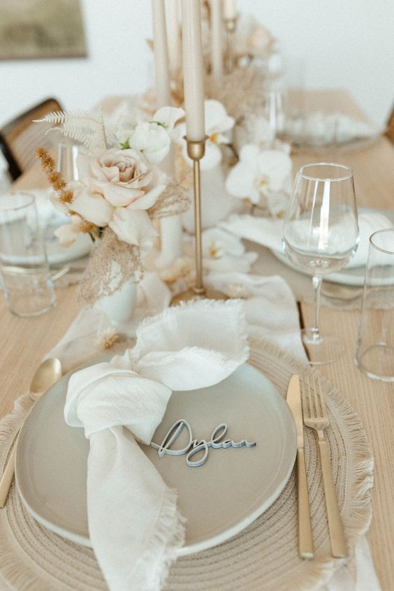 a subtle and chic greige wedding tablescape with a greige woven placemat and matching plates, white napkins and a table runner, neutral blooms and greige candles