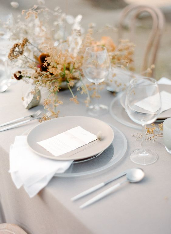 a subtle greige wedding tablescape with a greige tablecloth and plates, with bold blooms and greenery, white cutlery is a lovely idea for fall