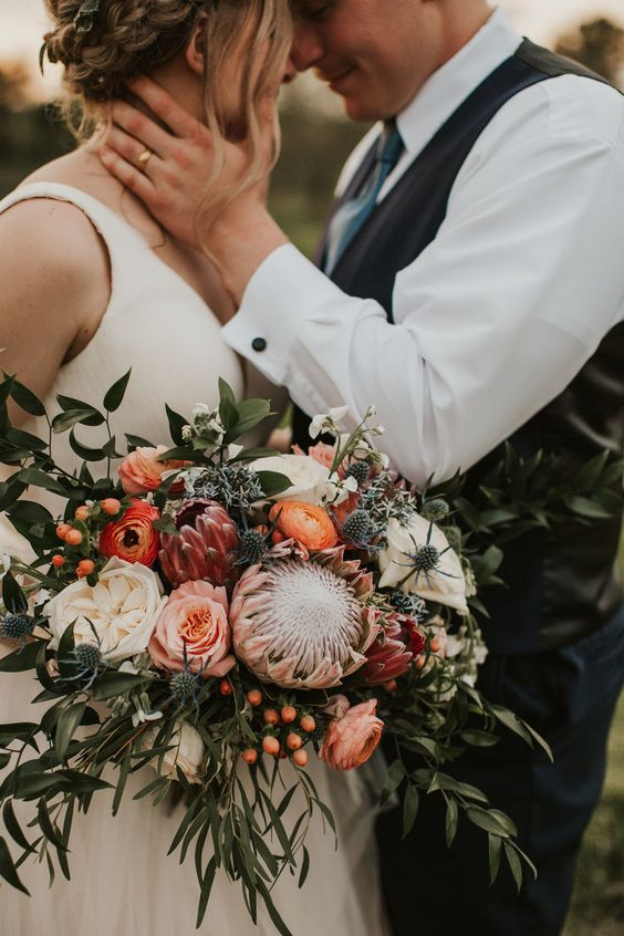 a subtle summer or fall wedding bouquet or orange, pink and neutral blooms, thistles, foliage and berries is a pretty idea for the fall