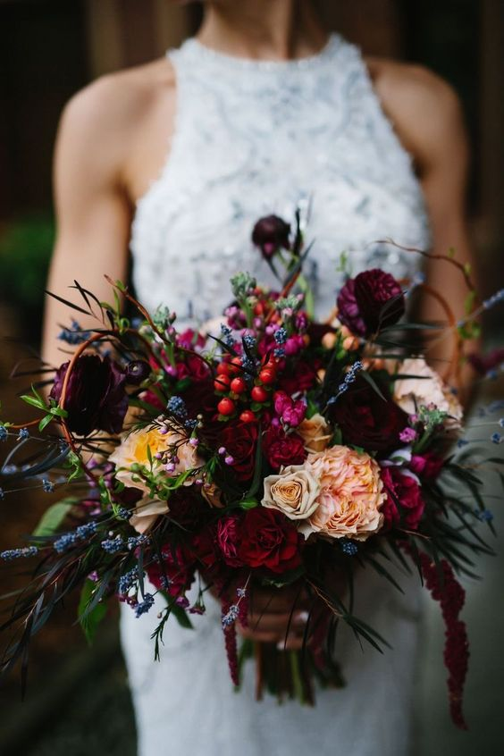 a sumptuous color wedding bouquet with fuchsia, deep red and hot pink blooms, lavender, greenery and some berries for a bold fall wedding