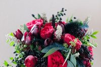 a sumptuous fall wedding bouquet of deep purple, pink and red blooms, lots of privet berries and greenery plus feathers for a fall bride