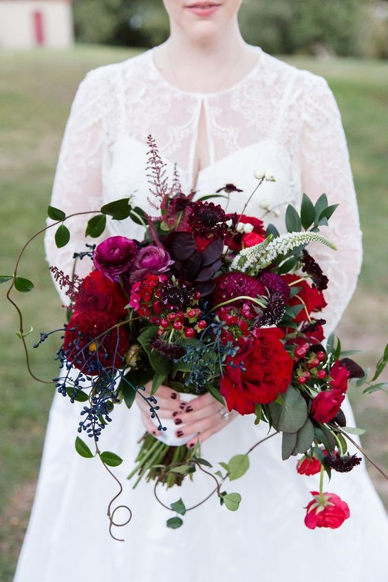 a super bold fall wedding bouquet that includes deep red, burgundy, fuchsia and deep purple blooms, greenery, foliage and privet berries