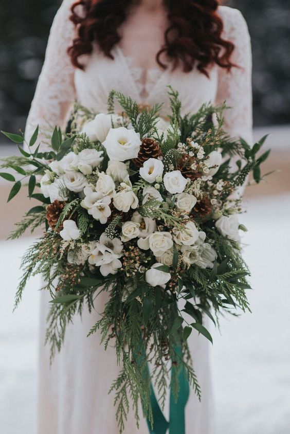 a super lush white wedding bouquet of blooms, greenery, fern, pinecones and long emerald ribbons is amazing for winter and can be rocked in the fall