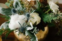 a textural and cool wedding centerpiece of a gilded vase with greenery, thistles, cotton, white and dried dark blooms and foliage is gorgeous