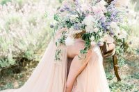 a textural and dimensional iridescent wedding bouquet with blush, white and lilac blooms and some cascading greenery