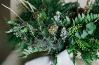 a textural greenery wedding bouquet with berries, seed pods, twigs and lots of foliage is a cool idea for a woodland bride