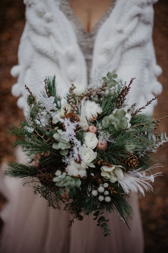 a textural winter wedding bouquet of evergreens, greenery, twigs, berries, pinecones, cotton, feathers and lotus is amazing