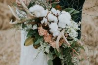 a textural woodland bouquet with antlers, cotton, gold and green leaves, pink and white blooms is a lovely idea for a boho or woodland bride
