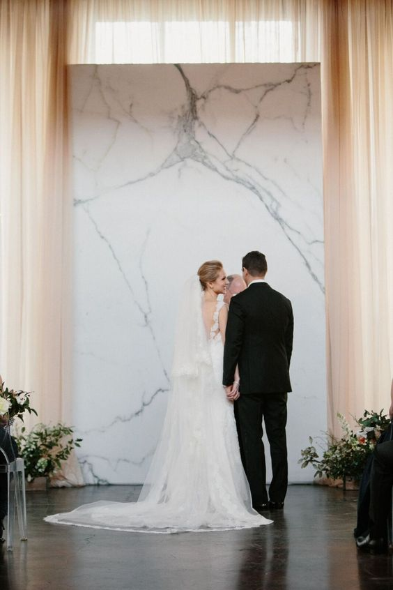 a timeless marble wedding backdrop with some greenery and blooms around is a gorgeous idea for a minimalist wedding