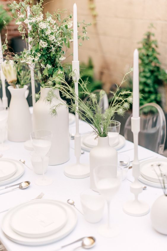 a very simple and minimal wedding tablescape with all white everything, with greenery and white blooms, tall and thin white candles and some cutlery