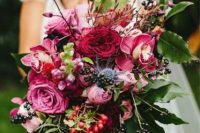 a vibrant fall wedding bouquet of pink and fuchsia blooms, various berries, foliage and twigs is a gorgeous solution for a fall bride