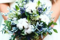 a wedding bouquet with cotton, greenery and blue thistles looks textural and very interesting is a lovely idea for a neutral winter wedding