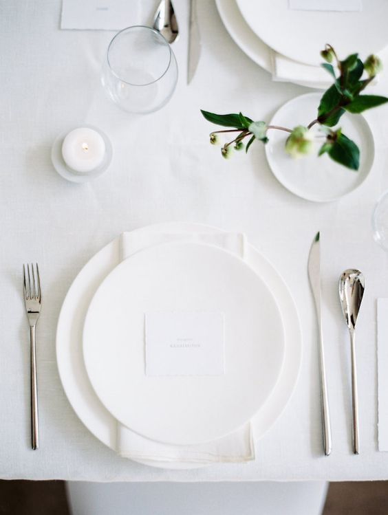 a white all-minimalist wedding tablescape with all white everything, some greenery to refresh the look and candles