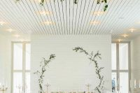 a white planked wall with greenery branches is an adorable idea for a rustic minimalist wedding and is easy to make yourself