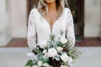 a white winter wedding bouquet of white blooms, pale leaves and greenery and pinecones is a perfect solution for a winter glam bride