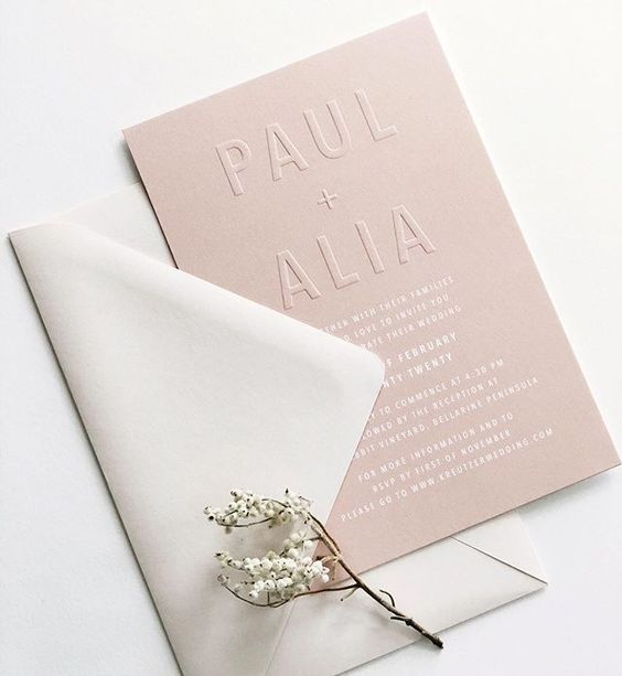 an airy minimalist wedding invitation suite with a dusty pink envelope and letter pressing, white printing and a neutral envelope