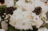 an all-neutral wedding bouquet of white roses, dahlias, berries, pinecones, evergreens and eucalyptus is a lovely idea for winter