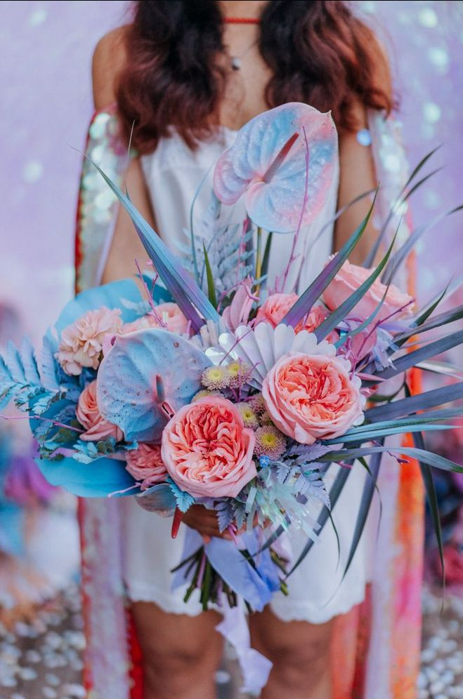 an amazing iridescent wedding bouquet with pink, blue, lilac blooms, grasses and fronds and with iridescent elements is wow