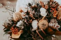 an earthy-colored textural boho wedding bouquet of rust, white and pink blooms, greenery, thistles and berries is cool for a boho wedding