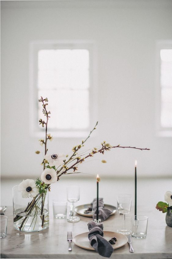 an elegant minimalist wedding table setting with neutral plates, grey napkins, white blooms, thin and tall black candles