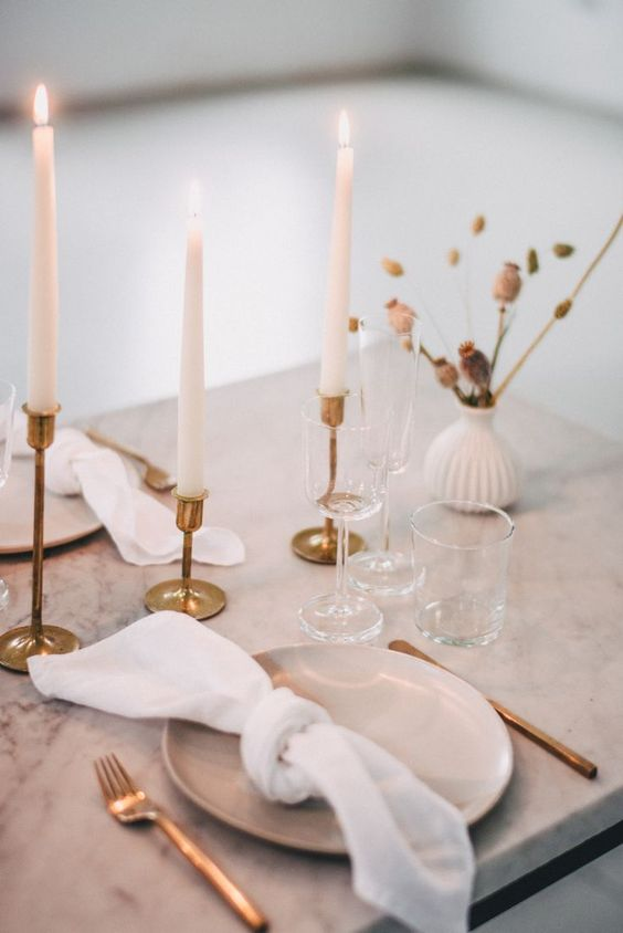 an elegant minimalist wedding tablescape with a marble table, tall and thin candles, dried blooms, gold cutlery and gold candlesticks