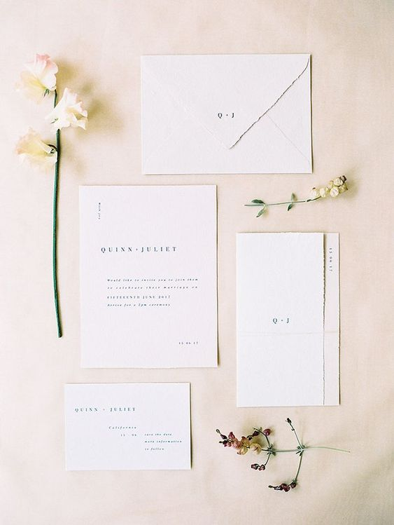 an elegant white minimalist wedding invitation suite with a raw edge and black lettering is a perfect idea for a minimal wedding