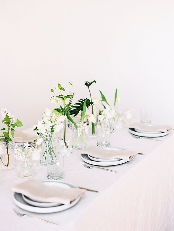 an ethereal minimalist wedding tablescape with all-neutral everything and some white blooms and greenery in jars to form a centerpiece
