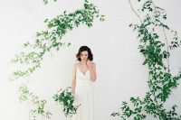 an ethereal wild vine wedding arch attached to the wall is a fab idea for a minimalist wedding with organic touches
